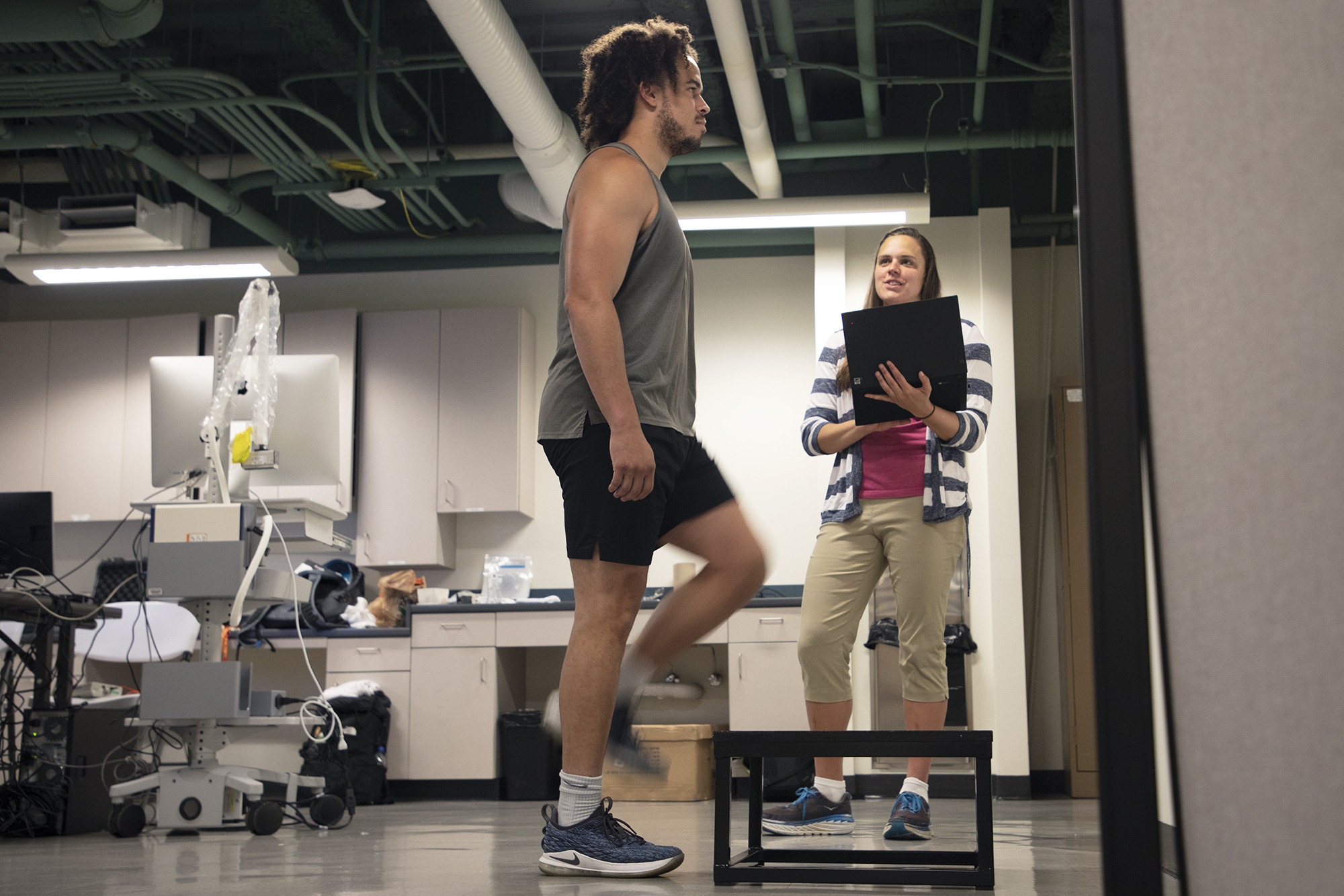 grad student Julianna Prim (right) monitors the heart rate of Ryan Brooks, as he steps up and down on a platform