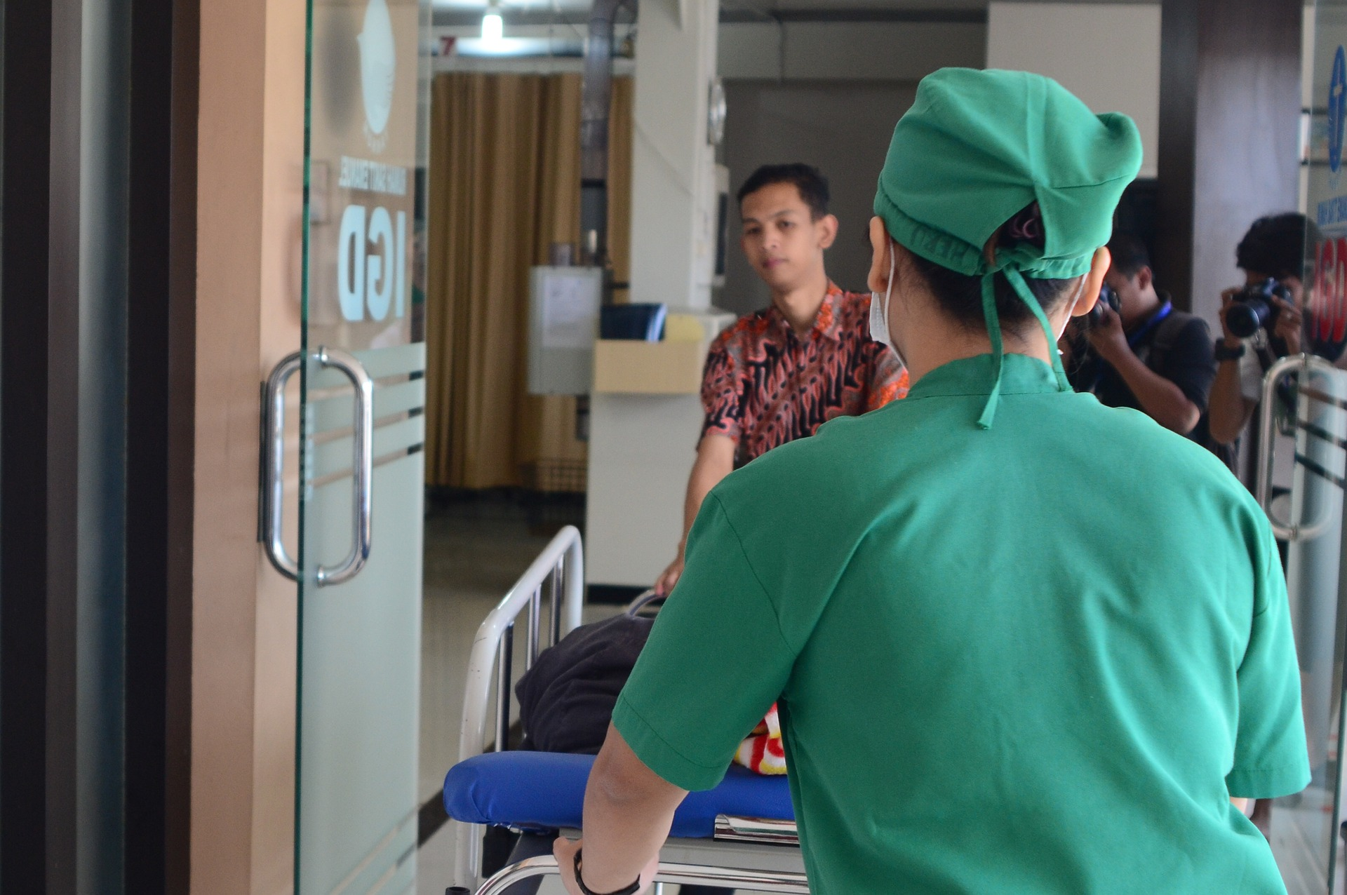 A patient is wheeled into the ICU by a doctor.