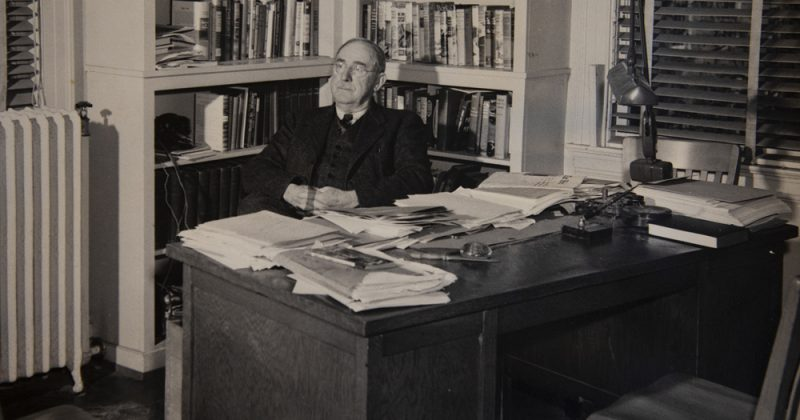 "Howard Odum sits in his ""famous"" office in the UNC Alumni Building. Much like his home office, it was covered in books and papers that he didn't allow anyone to reorganize. Photo courtesy of University Archives."