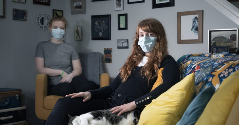 two young women wear masks as they sit in their living room