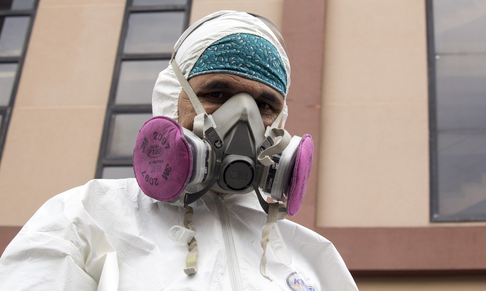 A man wears protective medical clothing and a face mask.