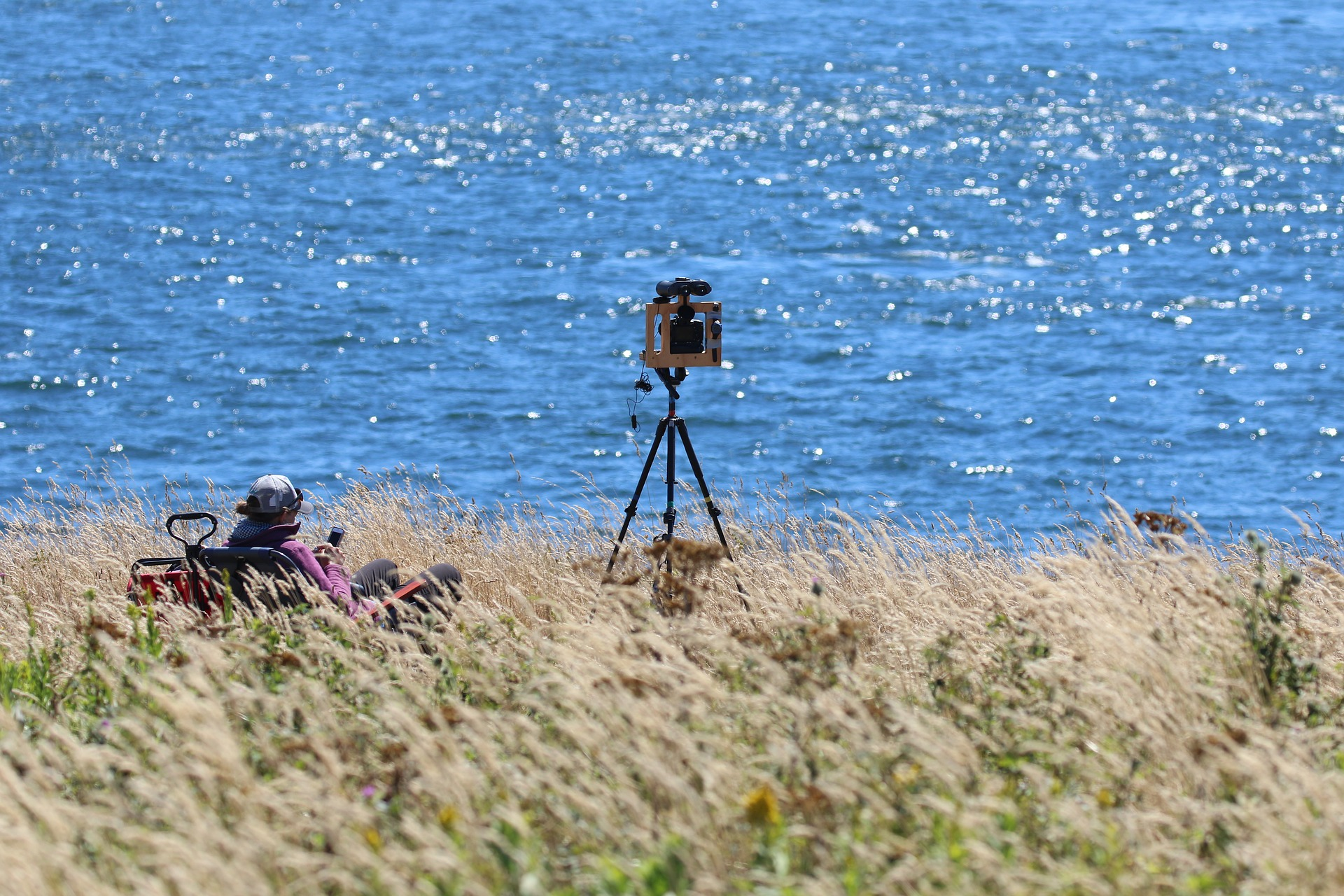 A lone researcher sits on a field near the ocean with a survey device.