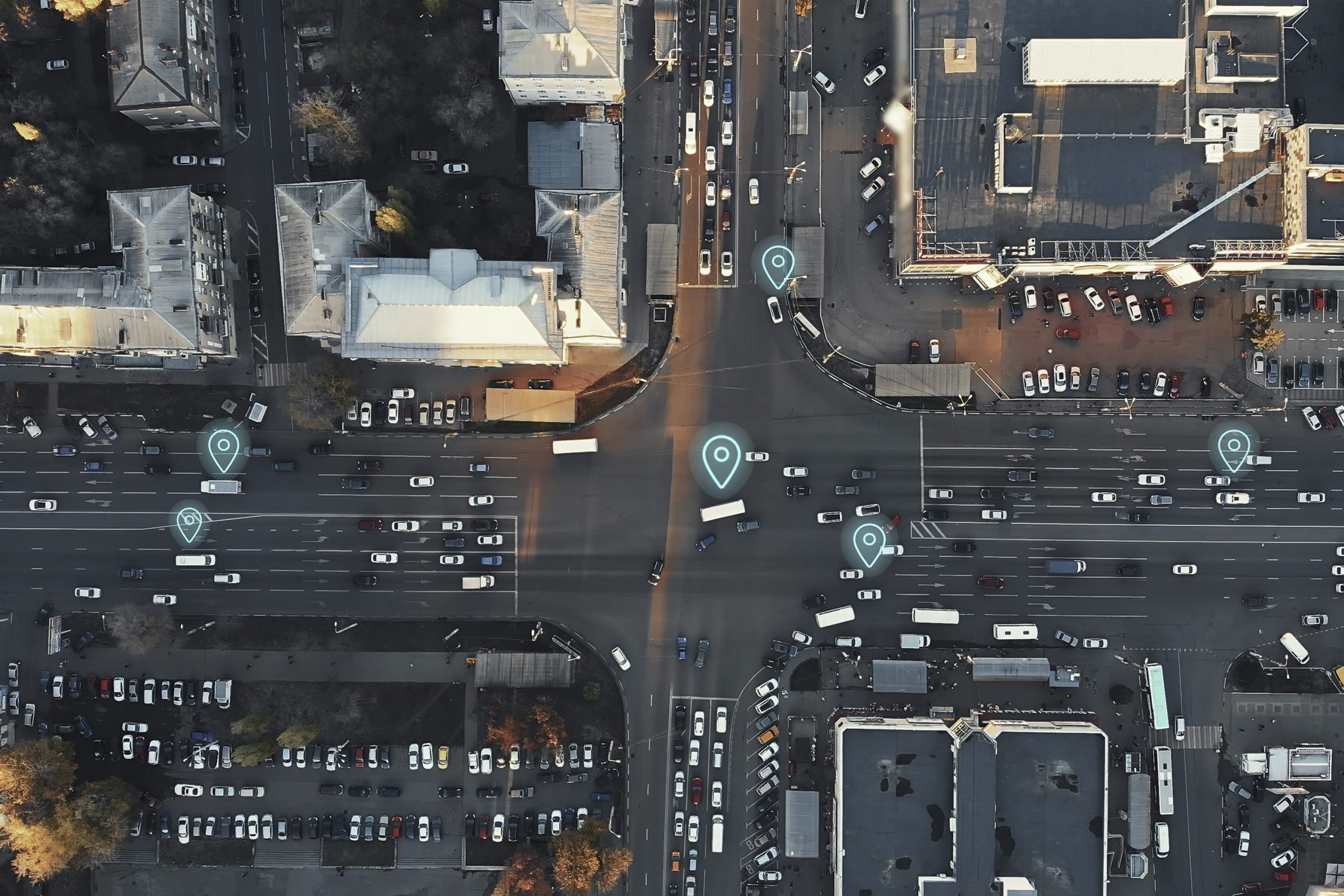an aerial view of four streets crossing with location icons on a few of the cars