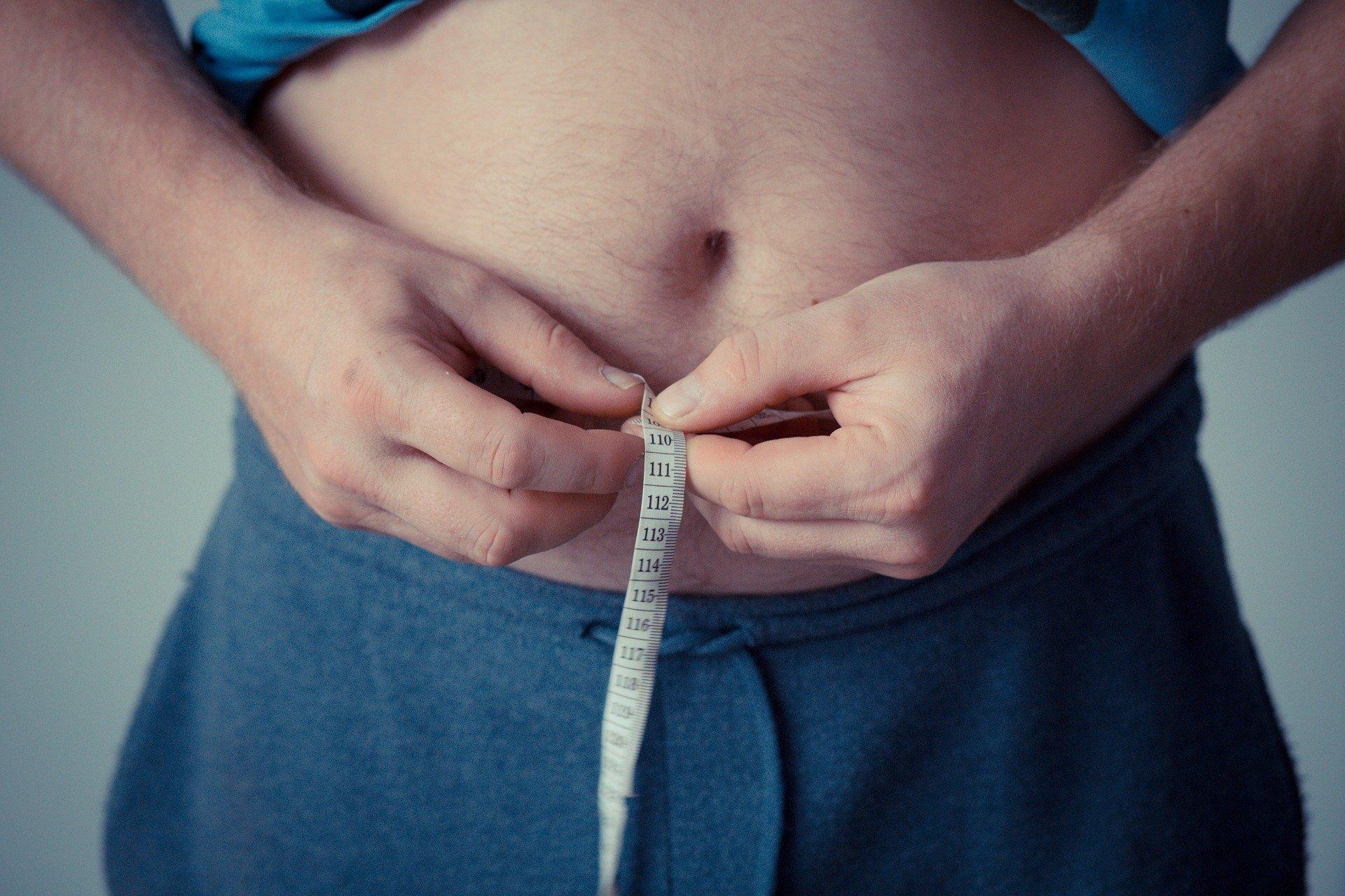 A man measure's his waist.