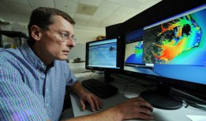 Rick Luettich sits in front of a computer with the ADCIRC Prediction System on the screen