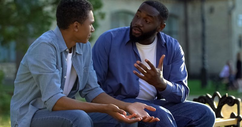 a black father talks with his son
