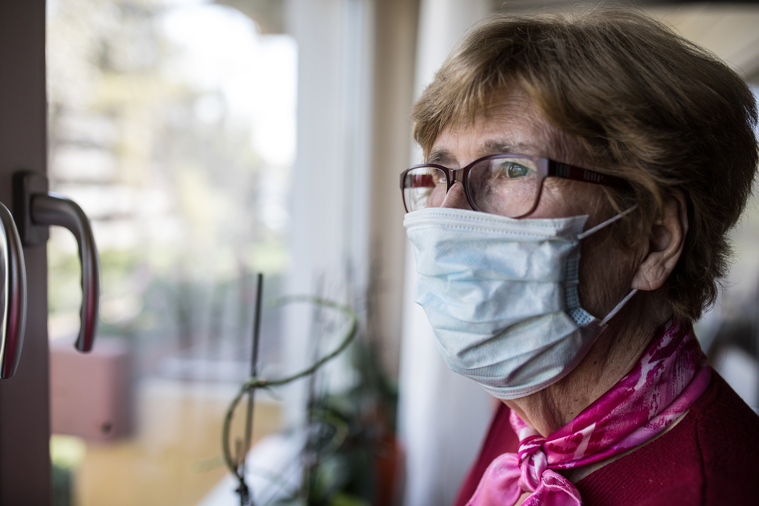 an elderly woman in a mask looks out in the window