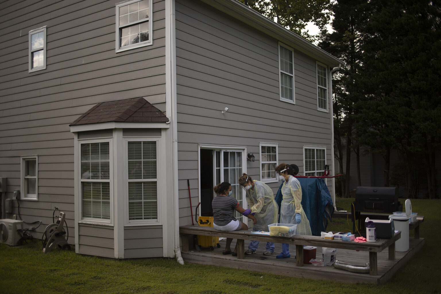 two researchers in full PPE collect blood and nasal swab samples from people on the back porch of their home