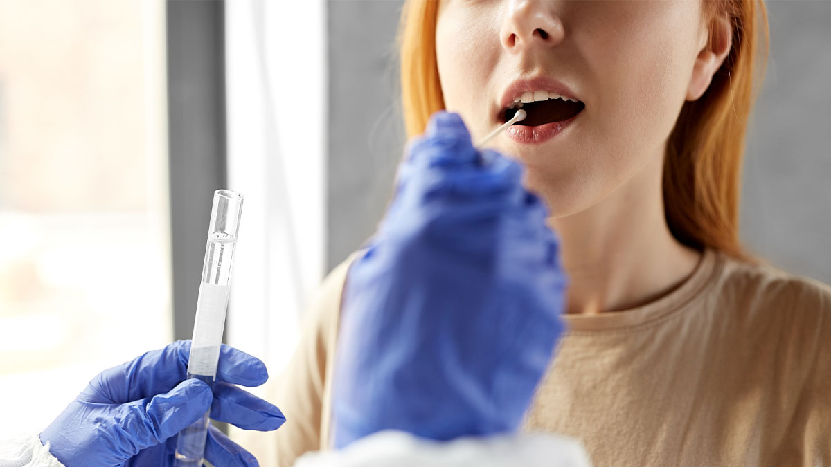 a gloved hand swabs a woman's mouth