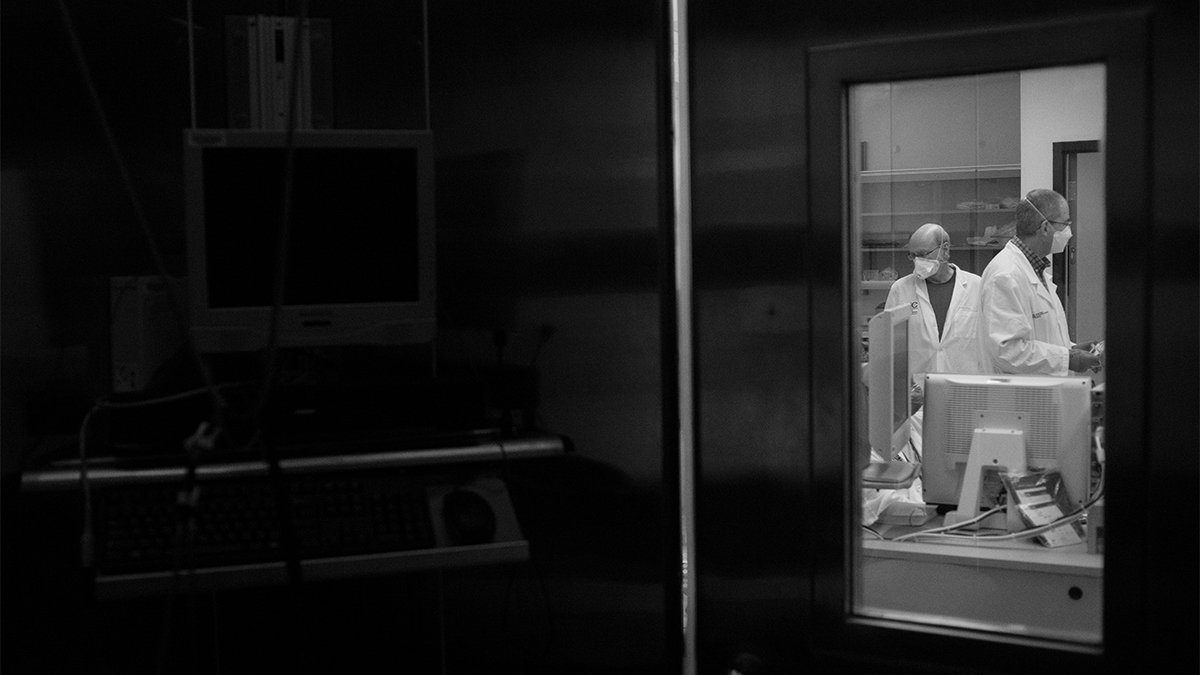 a sillhouette of researchers behind a class door wearing masks and conducting research