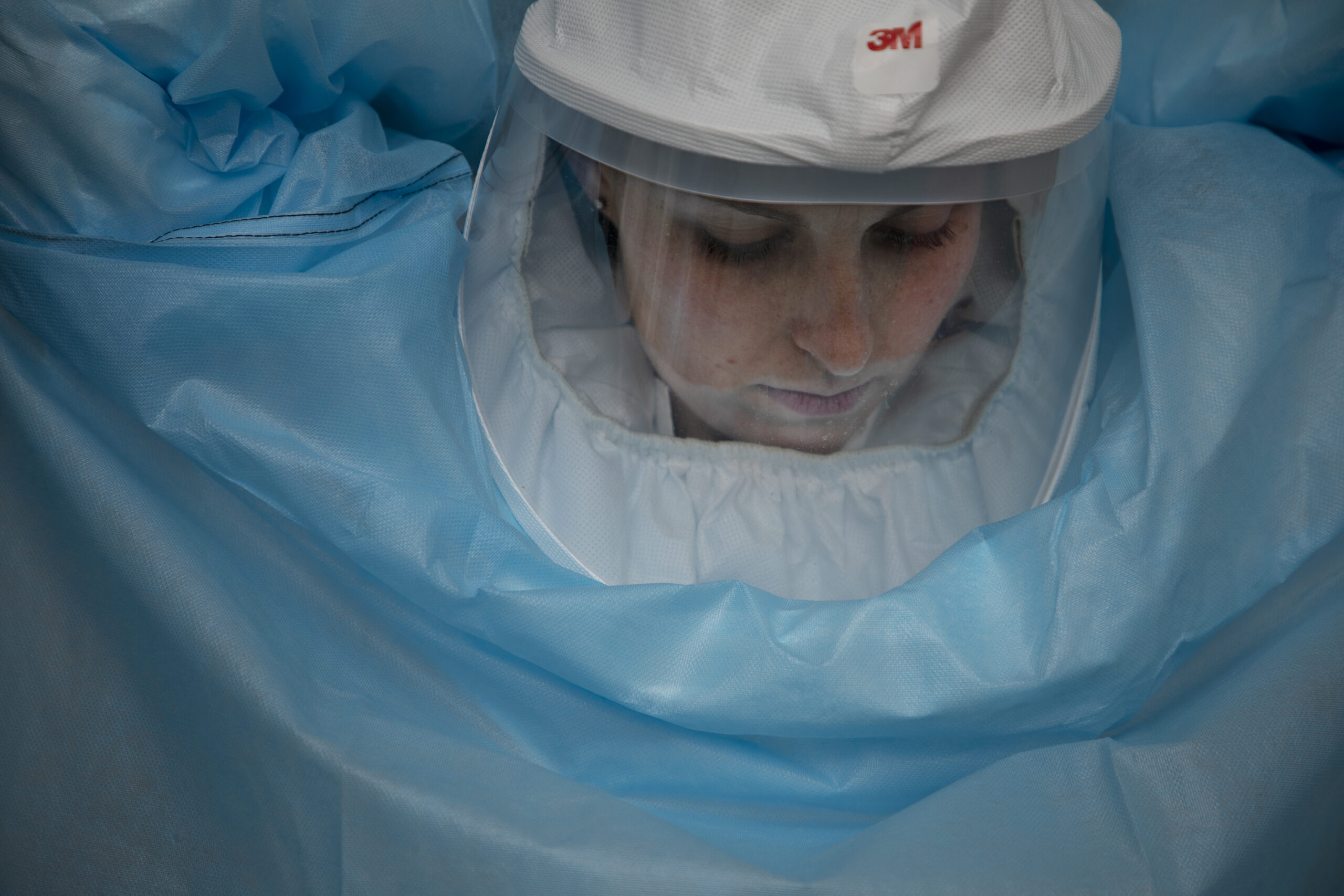 a young woman puts on a BSL3 suit