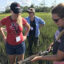 Carson Miller, a Carolina graduate student in the Rodriguez lab, demonstrates for teachers how to take soil cores in the salt marsh in 2019.