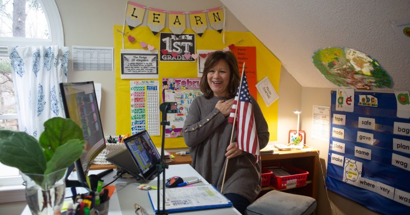 Suzanne Zaccardo holds an American flag and says the pledge of allegiance to her computer for her online class of first graders