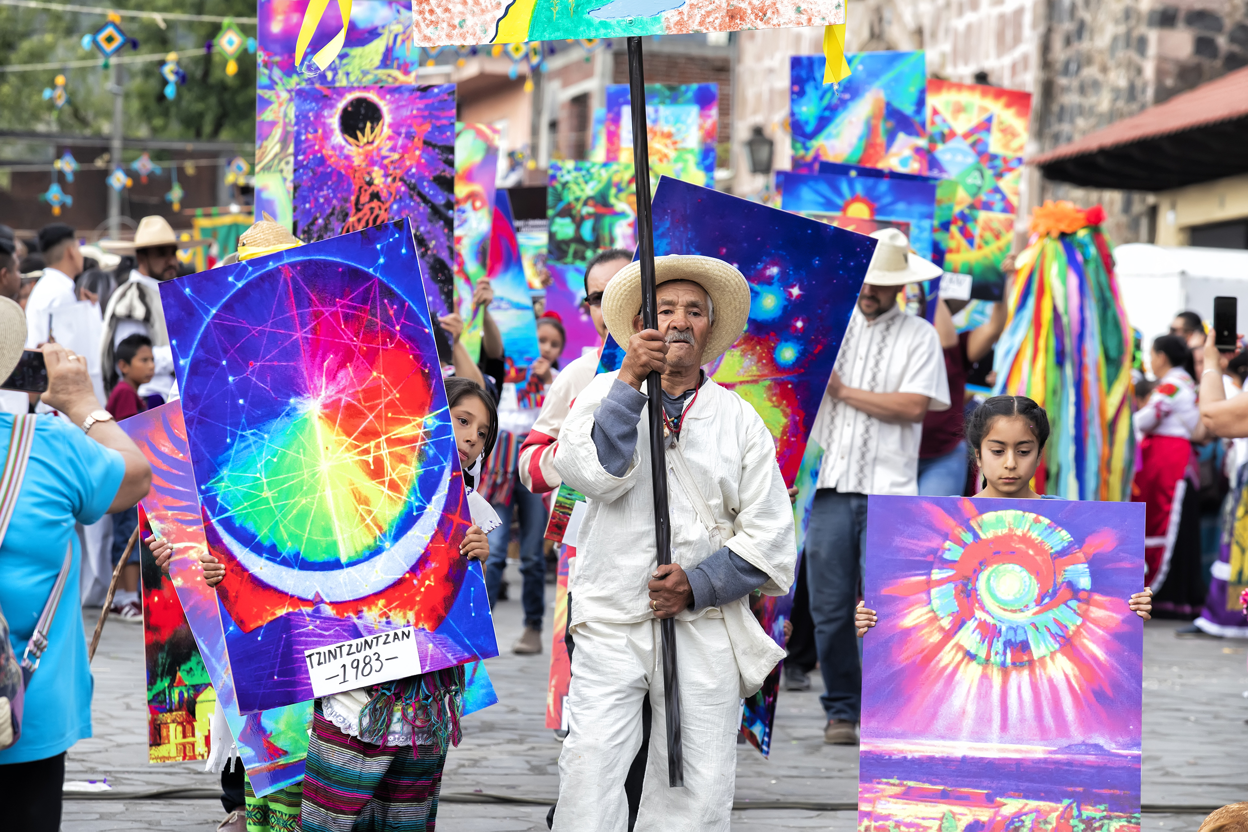 an elderly man and two young girls carry signs as part of a Mexican New Year celebration
