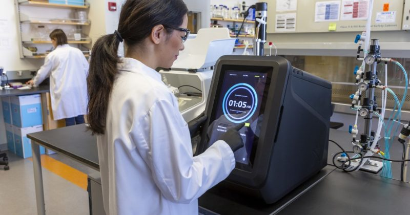 Photo: A woman wearing a white lab coat, glasses, black gloves, and a ponytail stands at a counter in a laboratory. She is using a large touch screen on a black device seated next to a metal cylinder covered in guages, switches, and tubes. Another woman in a white lab coat works in the background.
