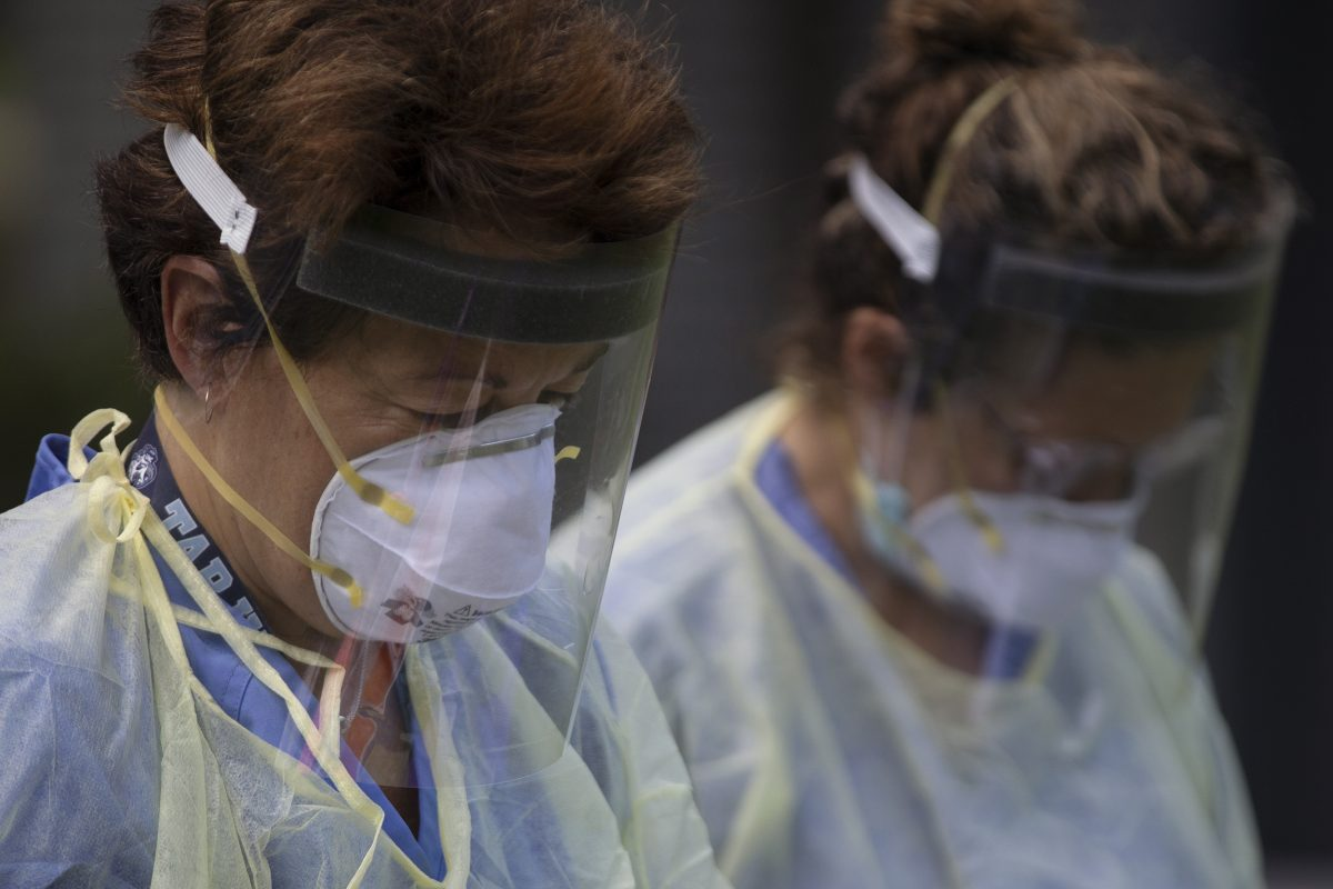 Photo: Two health care workers wear masks and face shields while conducting a study on COVID-19.