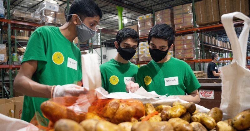 "Three students wearing masks and green ""Pantry Patrol"" t-shirts examine paperwork behind a bin of potatoes in a warehouse."
