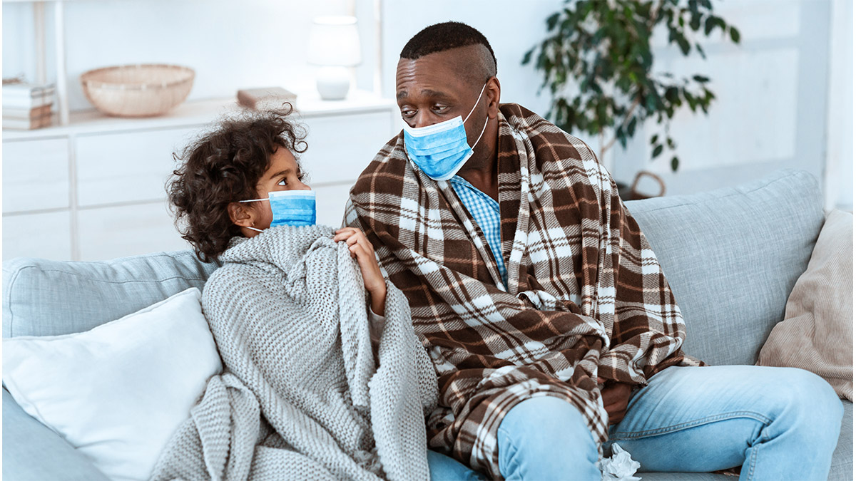 a father and daughter wear masks while sitting on the couch