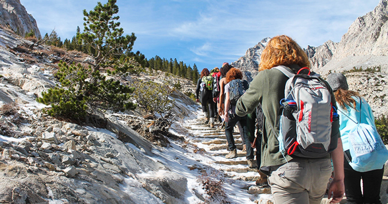 A line of people hiking away from the camera in mountainous terrain